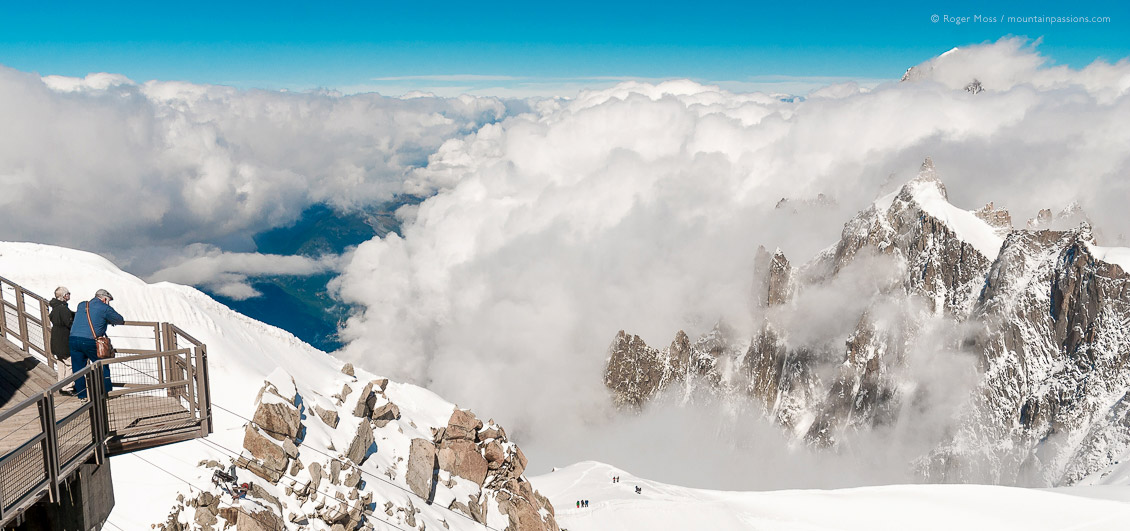 High view of visitors looking at Mont Blanc from observation deck of Aiguille du Midi, high above Chamonix