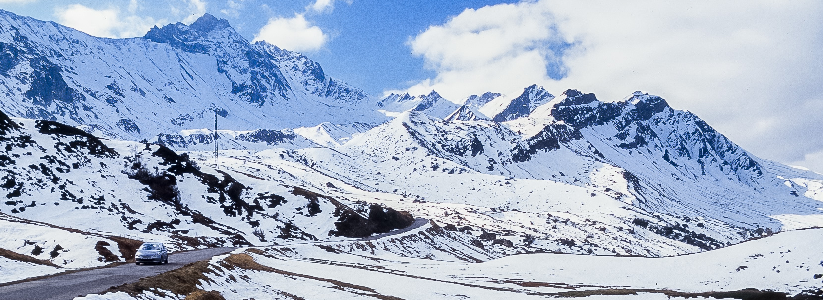 Wide view of Route des Grandes Alpes among snow-covered mountains