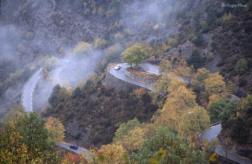 Cars negotiating one of the hairpin sections below the Col de Turini