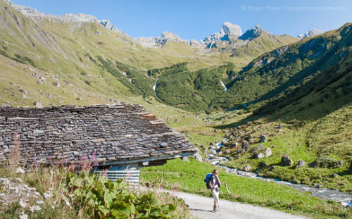 Walker passing mountain chalet near La Conchette, in summer in the Beaufortain, French Alps.