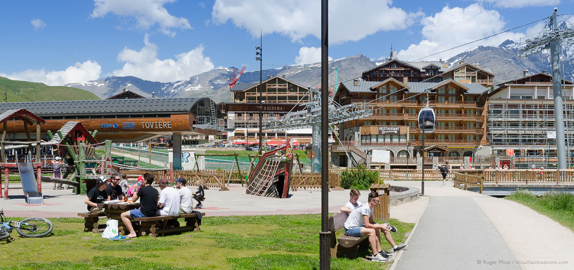 View of apartments and chairlifts with summer visitors in Tignes
