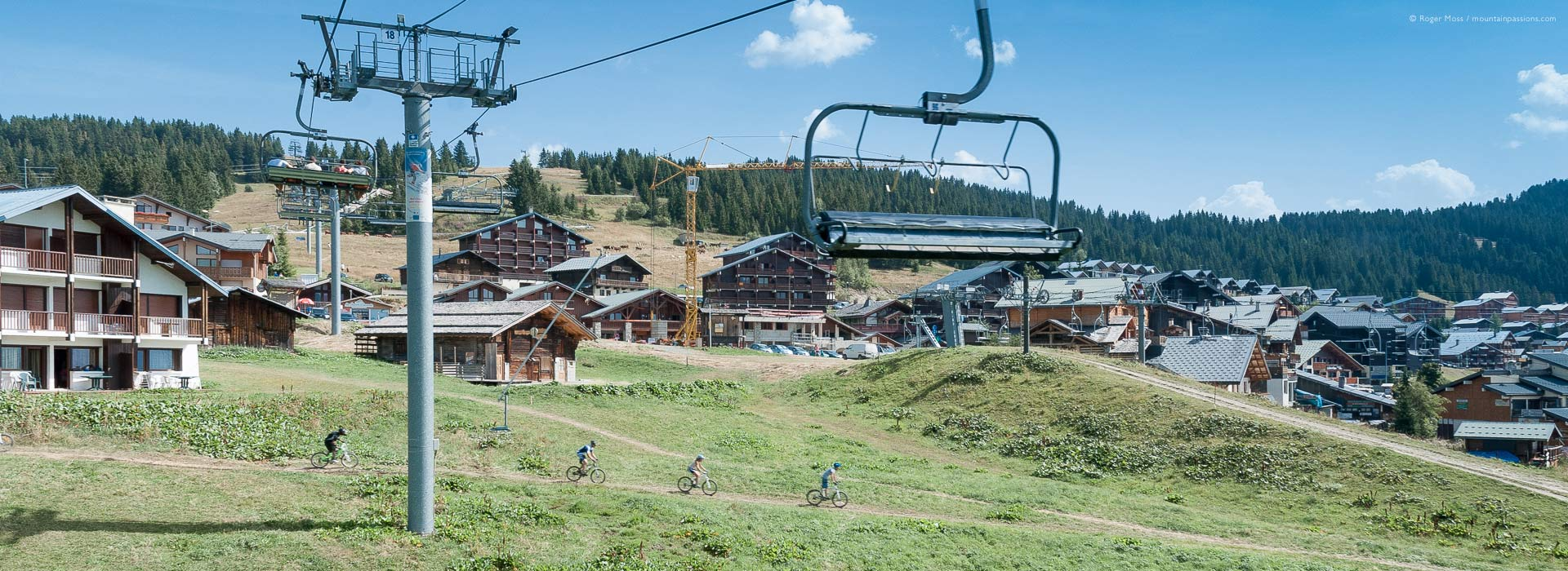 Wide view from chairlift of Les Saisies village with mountain-bikers