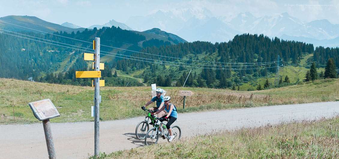 Two mountain bikers on track above Les Saisies with Mont-Blanc