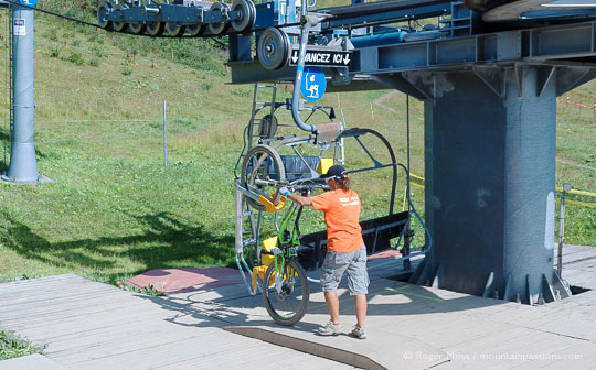 Lift operator loading mountain bike onto chairlift at Les Saisies