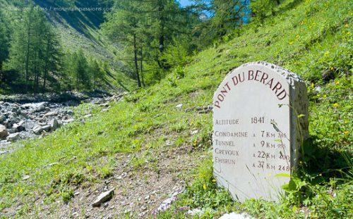 Stone sign at Pont du Berard, beside mountain stream.