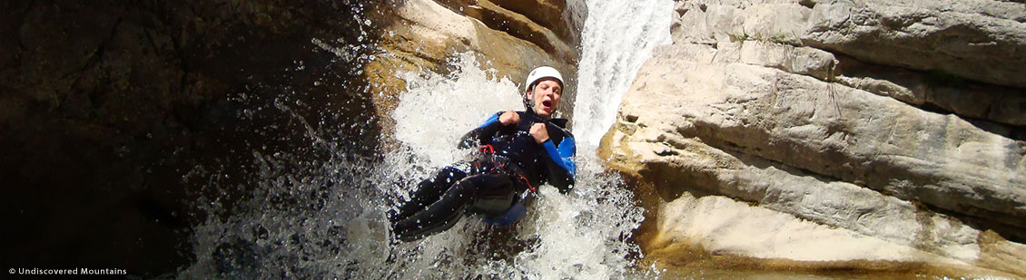 Canyoning - sliding down a waterfall in the southern French Alps.