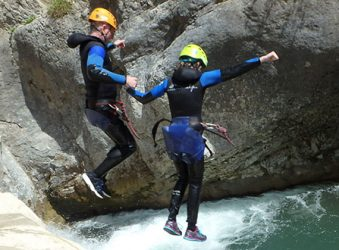 Canyoning couple holding hands, jump into pool.