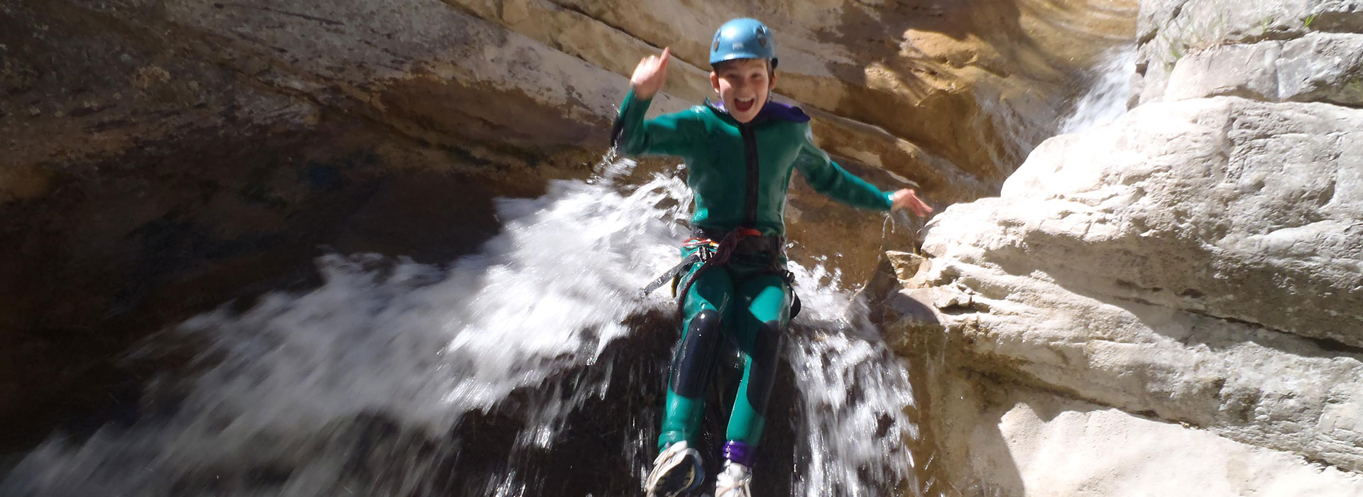 Canyoning in the southern French Alps - boy jumps over a waterfall.