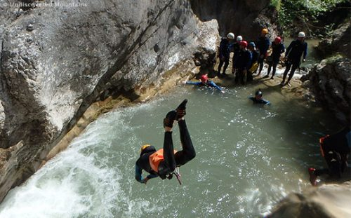Big dive into a pool with canyoning group in the southern French Alps.