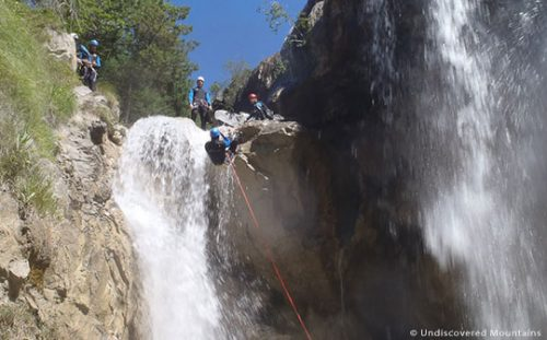 Canyoning group watch person abseil over waterfall  in southern French Alps