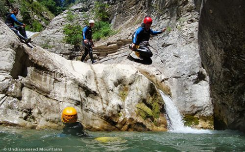 Group canyoning, jumping into pool.