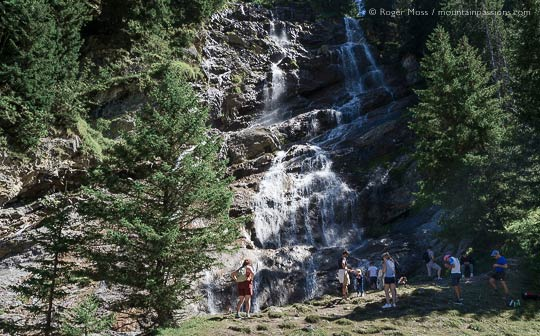 Walkers beside rockface among trees with waterfall