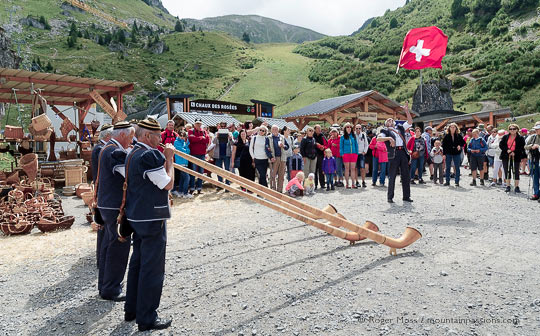 Alpine horn players with visitors surrounded by mountains at alpine festival above chatel, French alps
