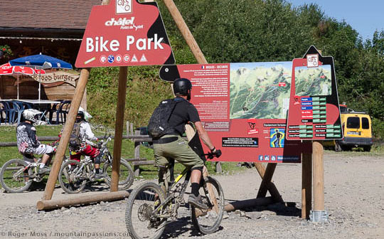 Mountain biker looking at map of Chatel bike park, French Alps