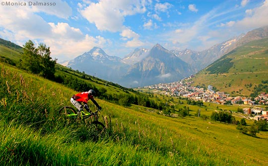 Mountain biker on the slopes above Les deux Alpes village in the summer