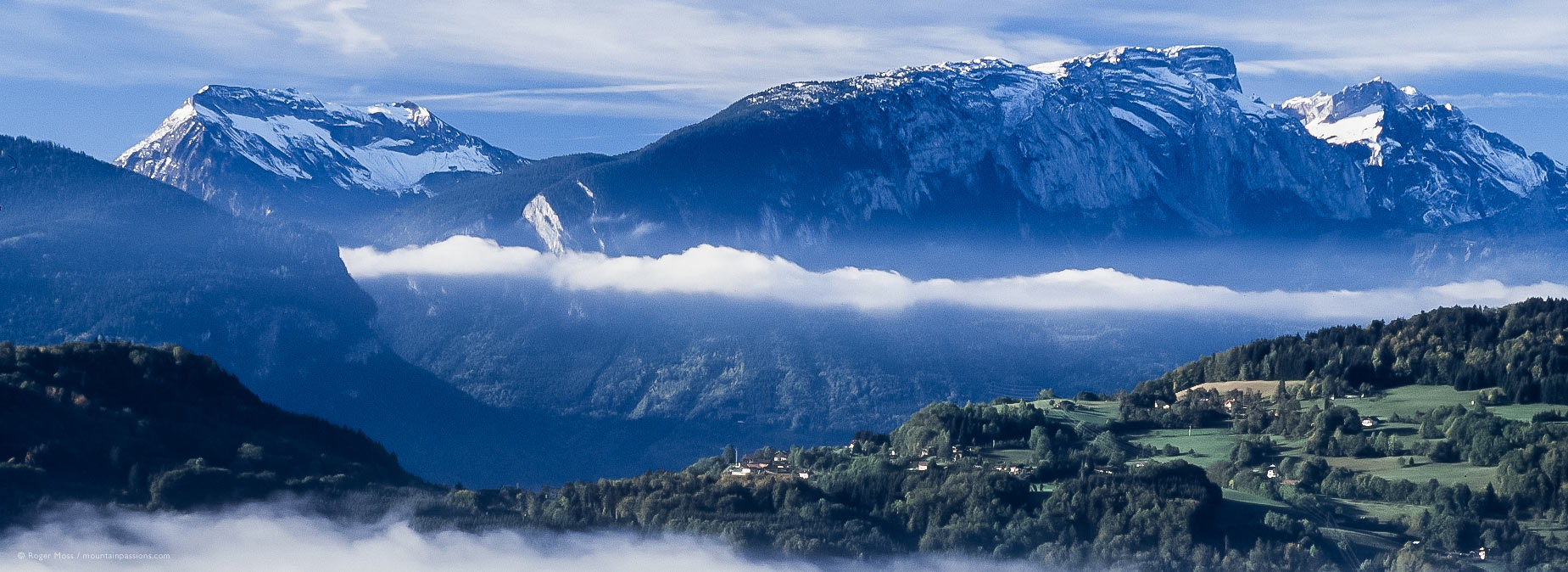 Wide overview of mountain landscape with morning mist from Route des Grandes Alpes above Tanninges, French Alps.