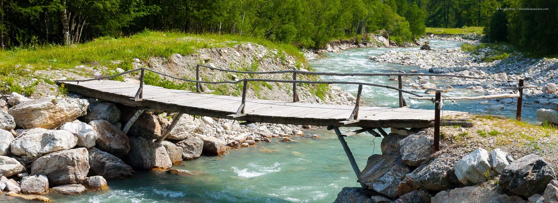 View of rustic wooden footbridge over mountain stream